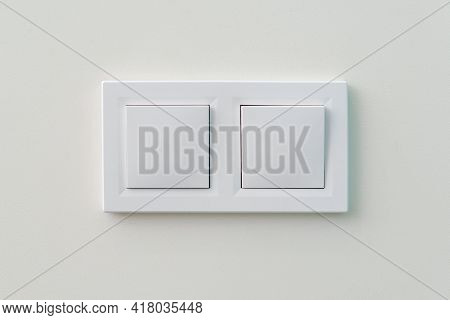 White Light Switch On The Wall. Turn On Or Turn Off The Lights. Wall-mounted White Double Light Swit