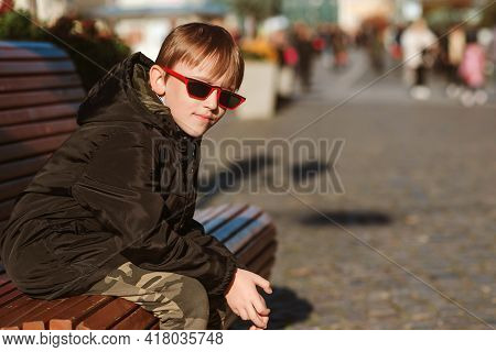 Handsome Boy Sitting On The Bench In The City. Preteen Boy Wearing Black Jacket And Trendy Sun Glass