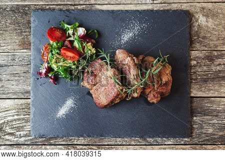 Grilled Beef Steaks On Black Stone Slate, Top View. Tasty Juicy Grilled Steak And Salad With Tomatoe