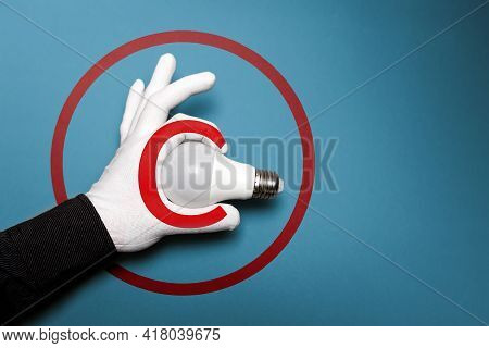 International Intellectual Property Day. A White-gloved Hand Holds A Light Bulb. Blue Background Wit