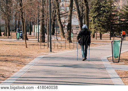 Man With Tourists Sticks Walks Alone In The Park Using . Back View. Strolling Through The Pathway. N