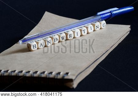 Blue Fountain Pen, Eco-friendly Notebook And Handwriting On A Dark Background. Concept Of Handwritin