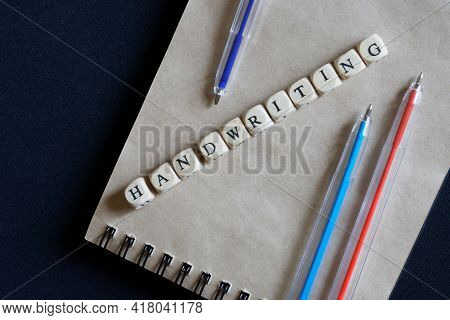 Multi-colored Ballpoint Pens, A Notebook And The Inscription