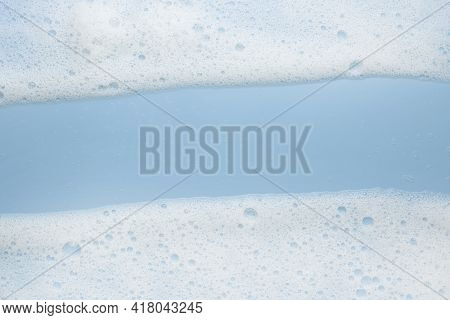 White Foam Mousse On A Blue Background. Frame Or Border For Their Foam Text. The Concept Of Foaming