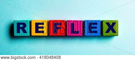The Word Reflex Is Written On Multicolored Bright Wooden Cubes On A Light Blue Background