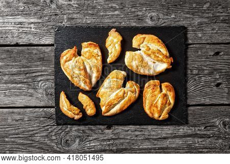 Flattened Roast Chicken Breasts On A Stone Tray On A Wooden Table, Horizontal View From Above, Flat
