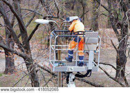 A Worker In An Orange Uniform Using A Construction Hoist Repairs Street Lighting On A Concrete Pilla