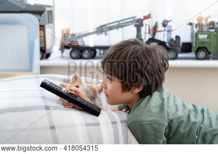 Portrait Of Happy Kid Lying On Sofa Watching Tv, Positive Child Boy Holding Remote Control Looking O