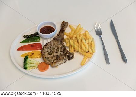 Grilled Meat, Porkchops Steak With Pepper Sauce And Salad. Grilled Pork Chop With Vegetable And Burr