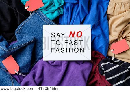 Say No To Fast Fashion Sign On Paper Card Over Heap Of Clothes. Fast Fashion Is Bad For The Environm