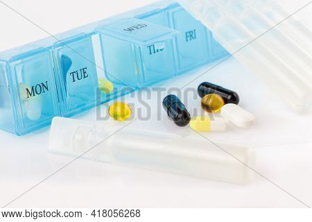 Pill Organizer With Variety Of Pills And Supplement. Weekly Pill Organizer On White Background. Dail