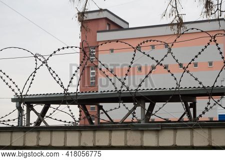 Barbed Wire On A High Fence. A Prison Behind Barbed Wire.