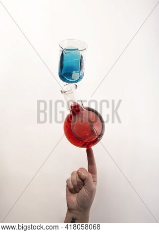 Flat Bottom Flask And A Berzelius Beaker Glass Balanced On Top Of Fingertip. Chemistry And Lab Instr