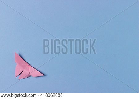 Pink Origami Butterfly Folds Out Of Paper. Blue Background With Copy Space. Education, Pastime, Hobb