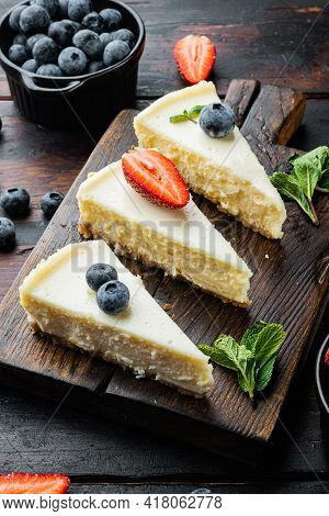 New York Cheesecake Or Classic Cheesecake With Fresh Berrie, On Old Dark  Wooden Table Background