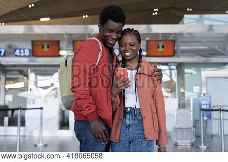 Loving Couple Waiting For Flight In Airport Terminal Hug, Take Selfie Photo On Smartphone. African M