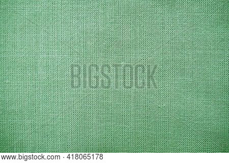 Texture Of Natural Green Fabric Close-up. The Texture Of The Fabric Is Made Of Natural Cotton Or Lin