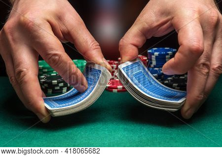 Close-up Hands Of Person-dealer Or Croupier Shuffling Poker Cards In A Poker Club On The Background