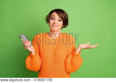Photo Of Uncertain Young Woman Shrug Shoulders Hold Smartphone Blogger Isolated On Green Color Backg
