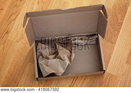Open Cardboard Box With Crumpled Paper Inside On A Wooden Background. Close Up.
