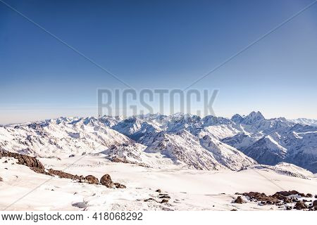 Panorama Of The Mountains From Elbrus. The Peaks Of The Caucasus Mountains Under Your Feet. White Mo