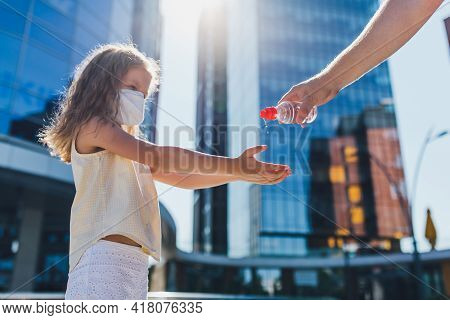 Mother Squeezing Hand Sanitizer Into Little Daughters Hand Outdoors To Prevent The Spread Of Viruses