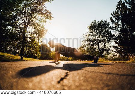 Man Do Push-ups At The Street, Crossfit Man And Lifestyle Concept. Doing Push Ups On Outdoors. Backg