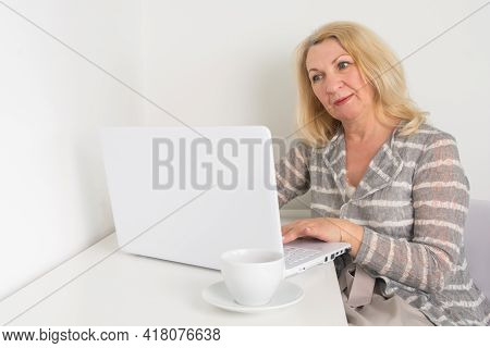 A Middle-aged Woman Sits At A Computer And Works Remotely. An Elderly Blonde Is Shopping Online.