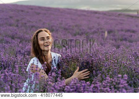 Close Up Portrait Of Happy Young Brunette Woman In White Dress On Blooming Fragrant Lavender Fields