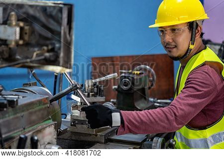 Asian Machinist In Safety Suit Operating The Professional Lathes In Metalworking Factory, Lathe Grin