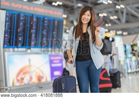 Portrait Of Asian Traveler With Luggage With Passport Standing Over The Flight Board For Check-in At