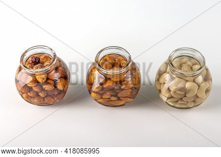 Process Of Soaking Various Nuts: Almonds, Hazelnuts, Cashew  In Water In Glass Jar To Activate. Home