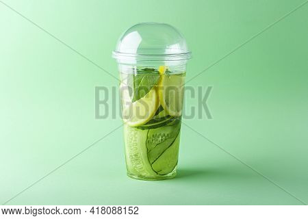 Fresh Cool Detox Drink With Cucumber, Lemon And Basil In Plastic Cup On Green Background. Tasty Infu