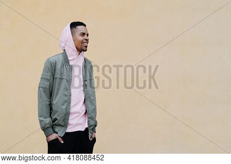 Afro Man Portrait Wearing Pink Parka With Hood On His Head Posing On Pale Yellow Background Looking
