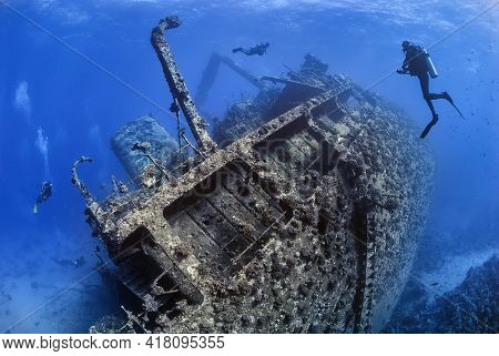 Divers Exploring The Outside Of A Shipwreck