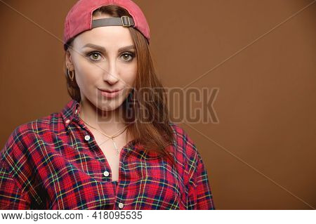 Portrait Of A Young Attractive Caucasian Woman In A Red Shirt And Cap On A Brown Background. Attract