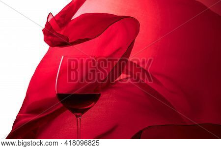 Glass Of Red Wine On A Background Of Waving Red Satin Curtain. Isolated On White.