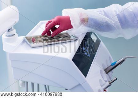The Dental Tool Used By Dentists In The Office. Close Up Hand Takes Dental Tools In A Dental Clinic.