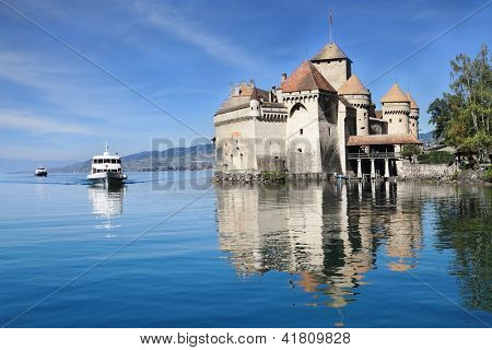 World-wide well-known Château de Chillon on Lake Geneva. The white tourist motor ship floats by a magnificent medieval castle poster