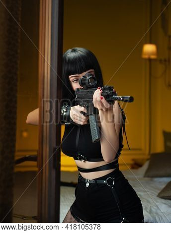 A Female Hitman In A Hotel Near The Window Aims An Automatic Rifle With A Telescopic Sight At The Vi