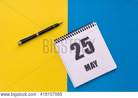 May 25th. Day 25 Of Month, Calendar Date. Notebook With A Spiral And Pen Lies On A Yellow-blue Backg