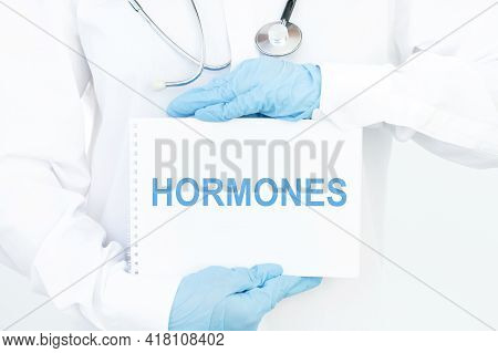 Notepad With Hormones Text In Doctor's Hands, Medical Concept