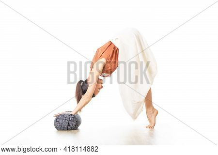 Restorative Yoga With A Bolster. Young Sporty Attractive Woman In Bright White Yoga Studio, Stretchi