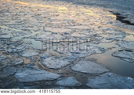 Reflection Of The Sunset In The Icy Moscow River.cracked Ice On The River. Pieces Of Ice On The Rive