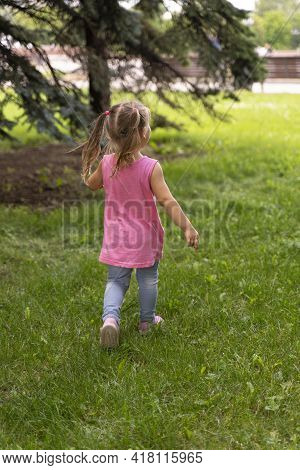 A Little Girl In A Pink Tunic Walks On The Grass In Sneakers