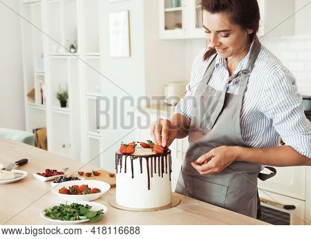 Pastry chef decorates the cake with berries