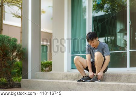 Asian Man Are Wearing Shoes On The Front Steps Of Their Homes To Jogging In The Neighborhood For Dai