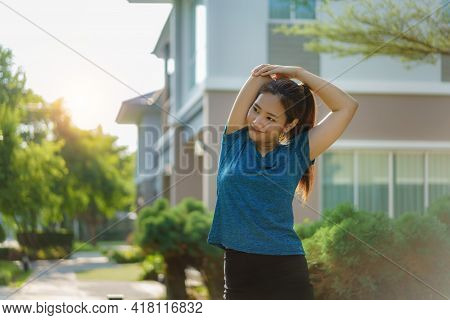 Asian Woman Stretching To Warm Up Or Cool Down, Before Or After Exercise, Near The Front Door In The