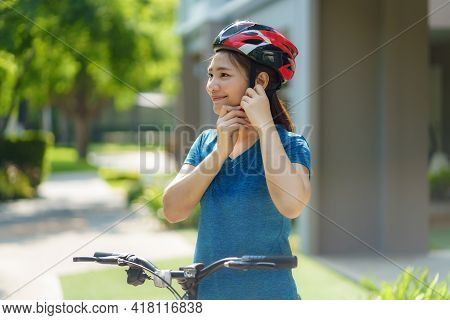 Asian Woman Wearing A Helmet While Preparing For A Bike Ride Around Her Neighborhood For Daily Healt