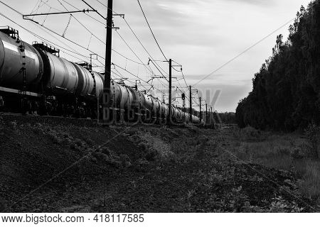 Railway Black-white Landscape. The Freight Train Goes Far. Transportation Of Goods And Fuel Tanks By